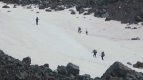 Туристы альпинистов людей пылают след на горе высоты снежной крутой видеоматериал