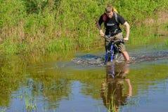 Туристы велосипеда идут вдоль затопленной дороги Стоковые Изображения RF