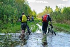 Туристы велосипеда идут вдоль затопленной дороги Стоковые Фотографии RF