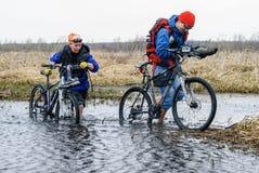 Туристы велосипеда идут вдоль затопленной дороги Стоковые Изображения