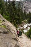 Туристы взбираясь вниз крутая скала Стоковое Фото