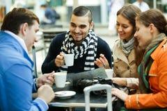Туристы выпивая кофе на кафе и читая карту города Стоковые Фото