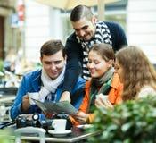 Туристы выпивая кофе на кафе и читая карту города Стоковая Фотография RF