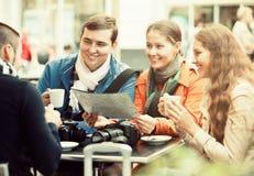 Туристы выпивая кофе на кафе и читая карту города Стоковые Изображения