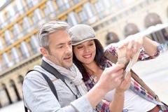 Туристы в городке смотря гида города Стоковые Изображения RF