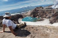 Туристы в кратере активного вулкана Gorely наблюдая на красивом озере кратера kamchatka Стоковое Фото