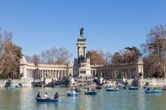 Туристы гребя традиционные голубые шлюпки на озере в парке города Retiro на славный солнечный зимний день в Мадриде, Испании стоковые фотографии rf