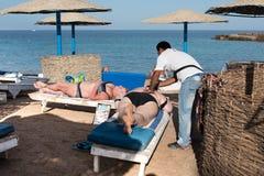 Туристы греют на солнце на пляже в Hurghada в Египте Стоковое Фото