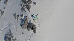 Туристы делают ангела в снеге на верхней горе на курорте пока путешествующ, взгляд трутня акции видеоматериалы