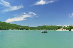 Туристы едут на маленькой лодке на живописном озере Abrau горы лето дня солнечное Стоковые Фотографии RF