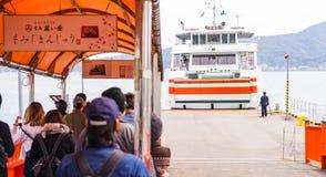 Туристы ждут для восхождения на борт парома МЛАДШЕГО к Miyajima Стоковые Фото
