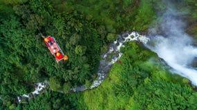 Туристы играют линию водопад застежка-молнии в Лаосе, тропическом лесе, Азии стоковые фотографии rf
