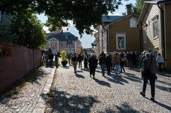 Туристы идут к старому квадрату в Porvoo, Финляндии Стоковые Изображения