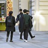 Туристы идут, подпирают взгляд 2 модных молодые люди в черноте стоковые фотографии rf