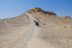 Туристы идя к Zoroastrian Dakhma Персидская башня безмолвия yazd Ирана стоковые изображения