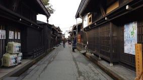 Туристы идя на городок Sanmachi Suji старый и традиционную японскую деревню в Takayama