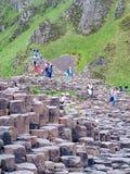 Туристы исследуют необыкновенные горные породы на гигантской мощёной дорожке ` s Стоковые Изображения