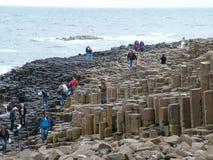 Туристы исследуют необыкновенные горные породы на гигантской мощёной дорожке ` s Стоковые Фото