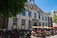 Туристы и местные люди наслаждаются голландским кафем расположенным около западного дома Индии в центре Амстердама, Нидерландов Стоковые Фотографии RF
