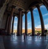 Туристы идут в тени величественных столбцов St Исаак Стоковые Изображения