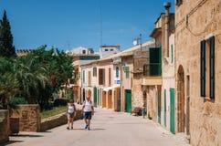 Туристы идя вперед на историческую часть городка Alcudia со своими традиционными домом и деревьями Стоковое Фото