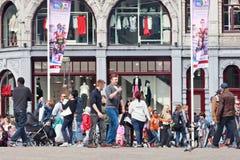 Туристы идя на crowdy квадрат запруды, Амстердам, Нидерланды Стоковая Фотография