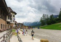 Туристы идя около здания укрытия Розы с лыжным курортом вертепа ресторана Стоковые Изображения RF