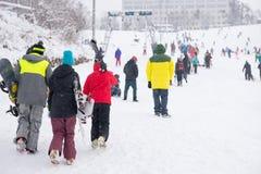 Туристы идя с трудом через снег на лыжном курорте Стоковые Изображения