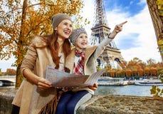 Туристы матери и дочери в Париже держа карту и указывать стоковая фотография rf