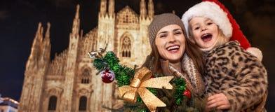 Туристы матери и дочери показывая рождественскую елку в милане стоковые фотографии rf