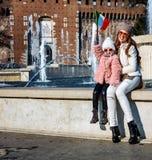 Туристы матери и ребенка около флага замка Sforza поднимая Стоковое Изображение RF