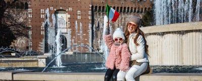 Туристы матери и ребенка около флага замка Sforza поднимая Стоковое Фото