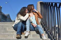 Туристы молодых дам сидя совместно на лестнице на обваловке реки Fontanka в Санкт-Петербурге России наблюдая туристские шлюпки да стоковые изображения