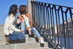 Туристы молодых дам сидя совместно на лестнице на обваловке реки Fontanka в Санкт-Петербурге России наблюдая туристские шлюпки да стоковое фото rf