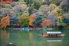 Туристы наслаждаются crusing в реке Hozu на Arashiyama во время красивого сезона осени Стоковые Изображения RF