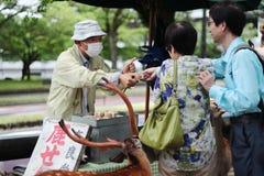 Туристы наслаждаются печеньями с оленями на sideway Стоковое Изображение