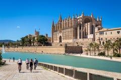 Туристы на велосипедах около главного собора Palma de Mallorca Стоковые Изображения RF