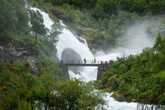 Туристы на мосте и водопаде брызгают ливень стоковые фото