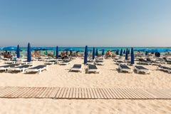 Туристы ослабляя на sunbeds на песчаном пляже под umbrel пляжа Стоковые Изображения RF