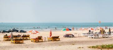 Туристы ослабляют на песчаном пляже с sunbeds и парасолем Стоковое Изображение