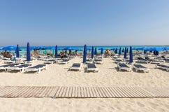 Туристы ослабляя на sunbeds на песчаном пляже под umbrel пляжа Стоковое Изображение RF