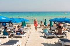 Туристы ослабляя на sunbeds на песчаном пляже под umbrel пляжа Стоковая Фотография