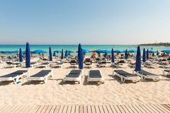 Туристы ослабляя на sunbeds на песчаном пляже под umbrel пляжа Стоковые Фото