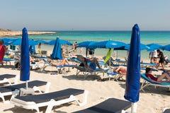 Туристы ослабляя на sunbeds на песчаном пляже под umbrel пляжа Стоковая Фотография RF