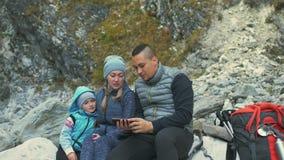 Туристы отдыхают после похода и принимают selfie по телефону перемещения семьи Окружающая среда людей горами, реками родители видеоматериал