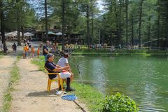 Туристы отдыхая простое озеро Ninfa на наклоне горы Monte Cimone, провинции эмилия-Романьи, Италии стоковая фотография