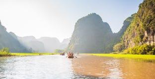 Туристы паромов лодочника вдоль залива Halong на достопримечательности земли в Tam Coc, Вьетнаме стоковое фото