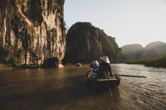 Туристы паромов лодочника вдоль залива Halong на достопримечательности земли в Tam Coc, Вьетнаме стоковое изображение rf