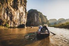 Туристы паромов лодочника вдоль залива Halong на достопримечательности земли в Tam Coc, Вьетнаме стоковые изображения rf