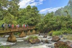 Туристы пересекая мост на Реку Parana в Игуазу Фаллс Стоковое фото RF